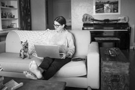 A young woman sitting on her couch with her dog using her laptop researching if she should buy a house or an apartment.