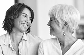Feel Good Wealth Your Community with a younger woman and older woman similing at each other.
