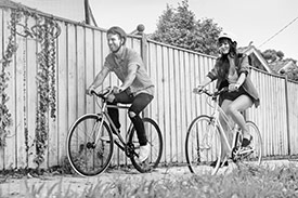 Feel Good Wealth Your Be Ethical with a man and woman each riding a bicycle in front of a wooden fence.